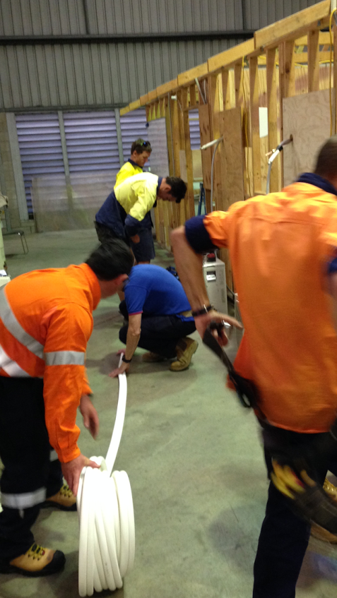 Unrolling pair coil at one of our air conditioning courses Adelaide wide.